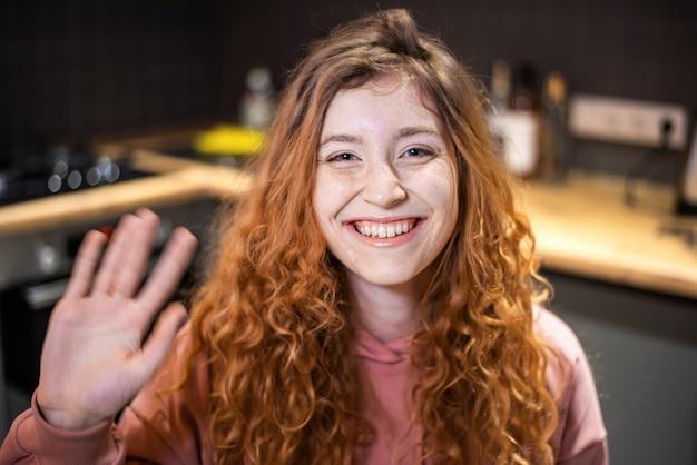 Porträt des jungen lächelnden mädchens mit ingwerhaar und winkender hand