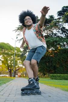Porträt des jungen lateinamerikanischen mannes, der fähigkeiten beim rollschuhlaufen im freien auf der straße übt. sportkonzept. stadtkonzept.