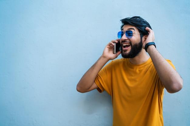 Porträt des jungen lateinischen mannes, der am telefon gegen blau spricht. kommunikationskonzept.
