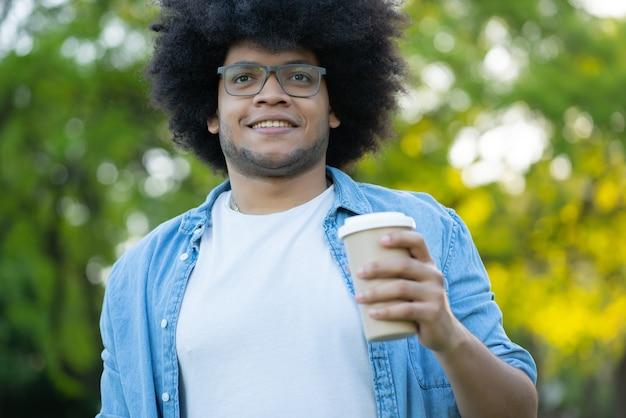 Porträt des jungen lateinischen mannes, der eine tasse kaffee hält, während draußen auf der straße geht