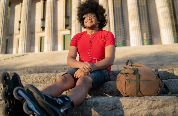 Porträt des jungen lateinischen mannes, der musik mit kopfhörern hört und sich nach dem rollschuhlaufen im freien ausruht. stadtkonzept.