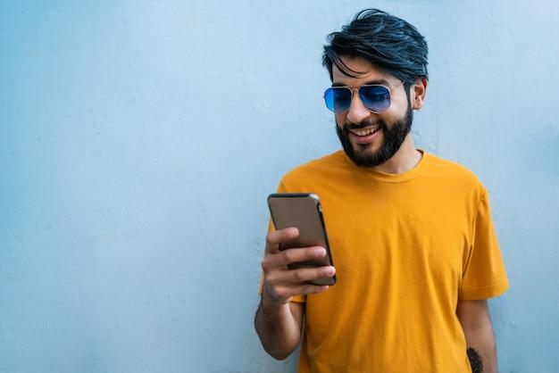 Porträt des jungen lateinischen mannes, der sein handy gegen den blauen raum benutzt. kommunikationskonzept.