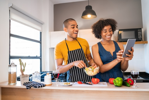 Porträt des jungen lateinischen paares, das ein digitales tablett verwendet und beim kochen in der küche zu hause lächelt. beziehungs-, koch- und lifestyle-konzept.