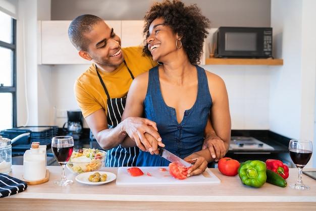 Porträt des jungen lateinischen paares, das zusammen in der küche zu hause kocht. beziehungs-, koch- und lifestyle-konzept.