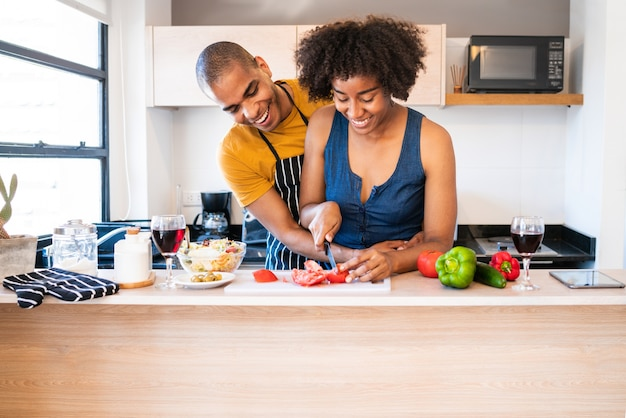 Porträt des jungen lateinischen paares, das zusammen in der küche zu hause kocht
