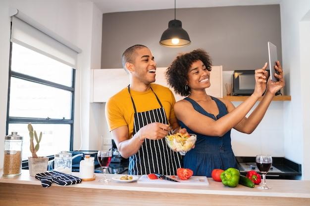 Porträt des jungen lateinischen paares, das zusammen kocht und ein selfie mit digitalem tablett in der küche zu hause nimmt. beziehungs-, koch- und lifestyle-konzept.