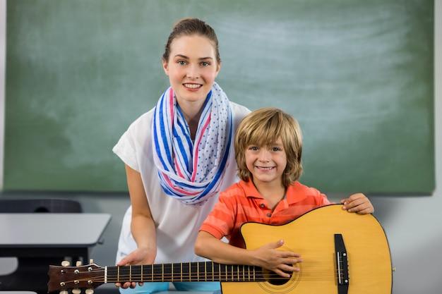 Porträt des jungen lehrers, der jungen hilft, gitarre zu spielen