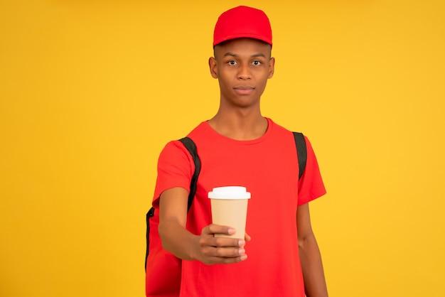 Porträt des jungen lieferboten, der eine tasse kaffee zum mitnehmen hält. lieferservice-konzept.