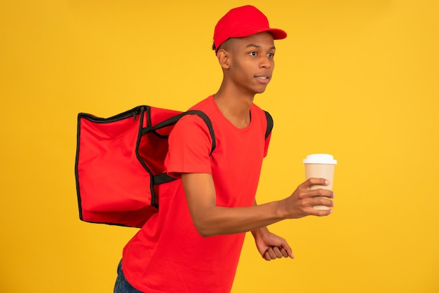 Porträt des jungen lieferboten in roter uniform, der mit einem kaffee zum mitnehmen läuft. lieferservice-konzept.