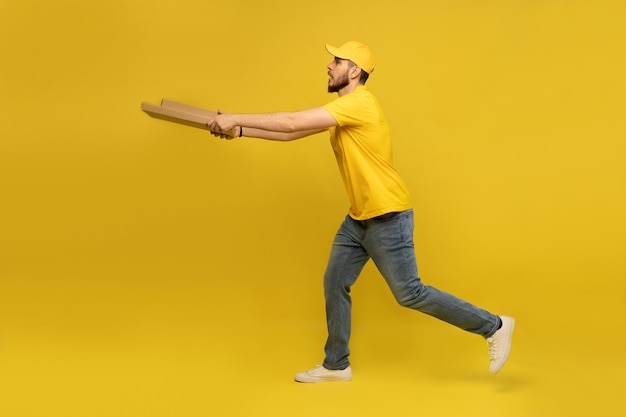 Porträt des jungen liefermanns in der gelben uniform mit pizzaschachteln lokalisiert über gelber wand