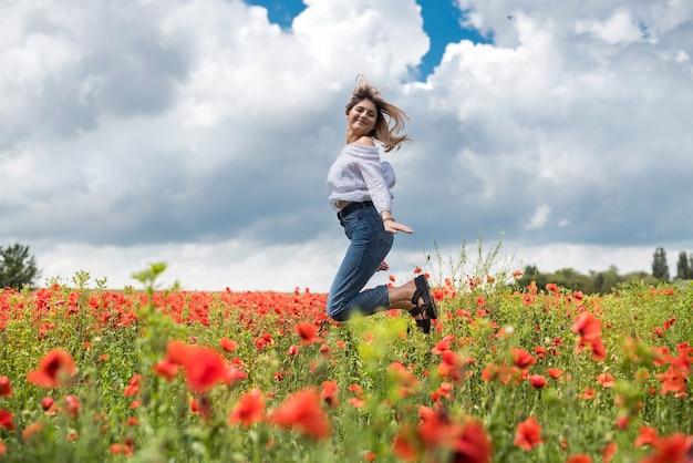 Porträt des jungen mädchens am roten mohnfeld. genieße es, zeit in der natur zu verbringen