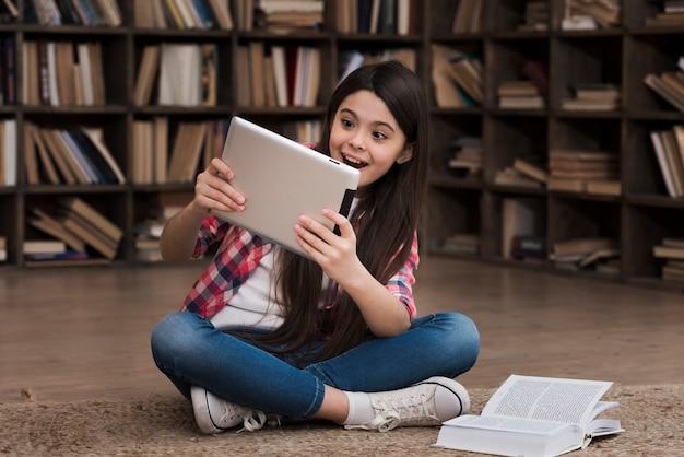 Porträt des jungen mädchens, das auf tablette an der bibliothek spielt