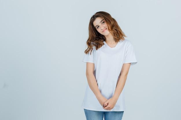 Porträt des jungen mädchens, das beim verbeugen des kopfes auf der schulter im weißen t-shirt aufwirft und fröhliche vorderansicht schaut