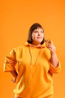 Porträt des jungen mädchens, das einen donut hält