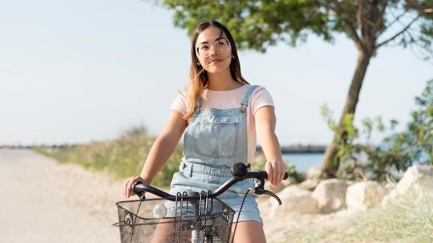 Porträt des jungen mädchens, das fahrrad draußen reitet