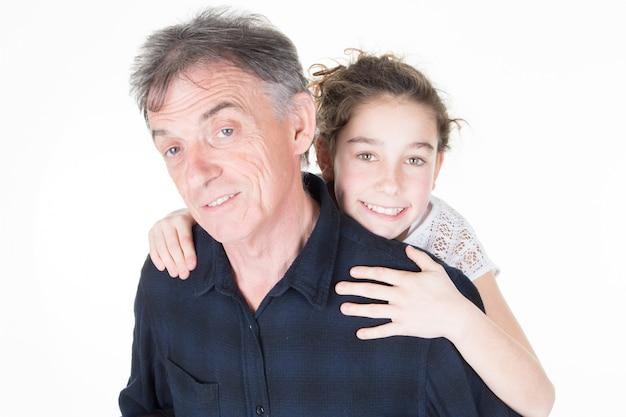Porträt des jungen mädchens, das großvater von hinten umarmt