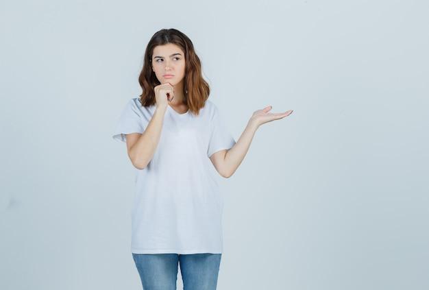 Porträt des jungen mädchens, das kinn auf hand stützt, handfläche in weißem t-shirt beiseite spreizt und nachdenkliche vorderansicht schaut