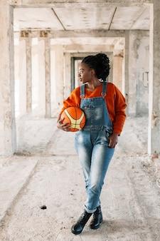 Porträt des jungen mädchens, das mit basketballball aufwirft