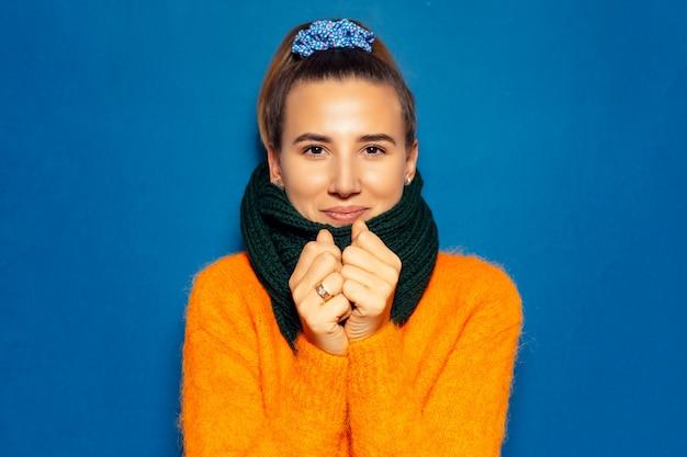 Porträt des jungen mädchens, das orangefarbenen pullover und grünen schal trägt