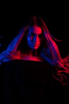 Porträt des jungen mädchens der mode im roten und blauen neonlicht im studio.