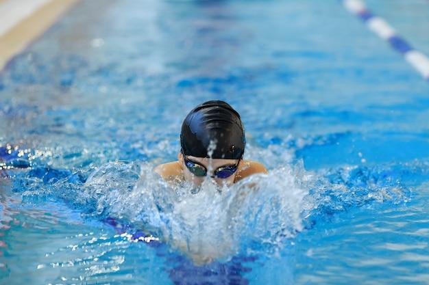 Porträt des jungen mädchens der nahaufnahme in der schutzbrille und in der kappe, die schmetterlingsanschlagart im blauen wasserpool schwimmt.