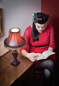 Porträt des jungen mädchens der schönen mode mit weißem make-up und tragendem retro- rotem kleid, das ein buch liest. klassisches konzept im vintage-stil.