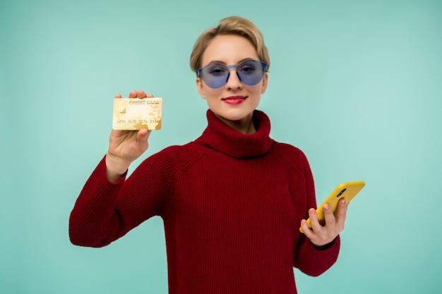 Porträt des jungen mädchens der schönheit, das plastikkreditkarte zeigt, während handy hält