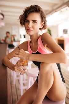 Porträt des jungen mädchens im badeanzug, der mit cocktail in der strandbar sitzt. schöne dame im trendigen badeanzug sitzt an der bartheke und schaut nachdenklich mit cocktail in den händen