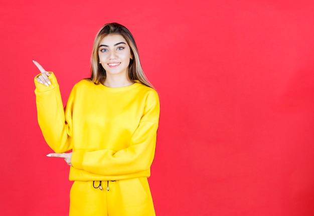 Porträt des jungen mädchens im gelben outfit, das auf roter wand steht