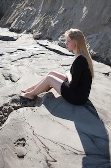 Porträt des jungen mädchens im schwarzen kleid mit langen blonden haaren, die am strand sitzen