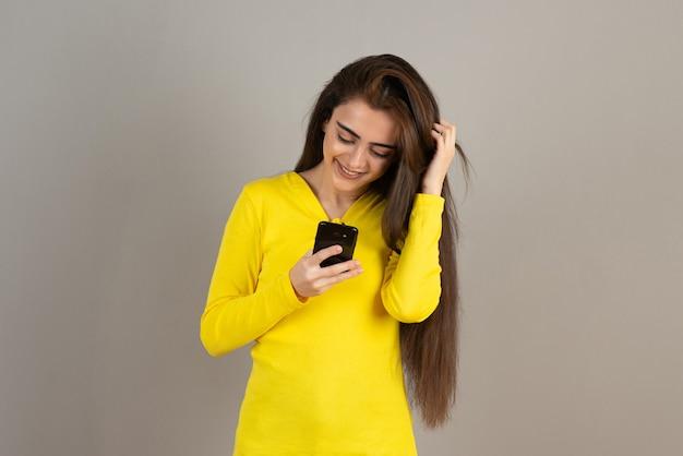 Porträt des jungen mädchens in der gelben spitze, die mobiltelefon auf grauer wand hält.