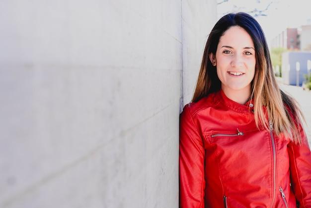 Porträt des jungen mädchens in der roten und blauen kleidung mit stolzer haltung von und von ihrer jugend.