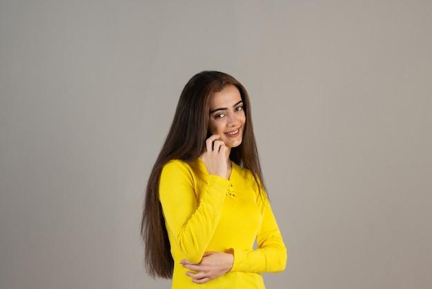 Porträt des jungen mädchens in gelb, das über handy auf grauer wand spricht.