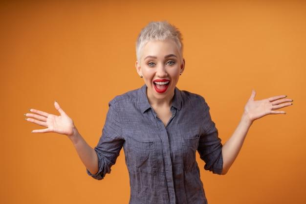 Porträt des jungen mädchens mit der blonden kurzen frisur, die kamera und lachen betrachtet