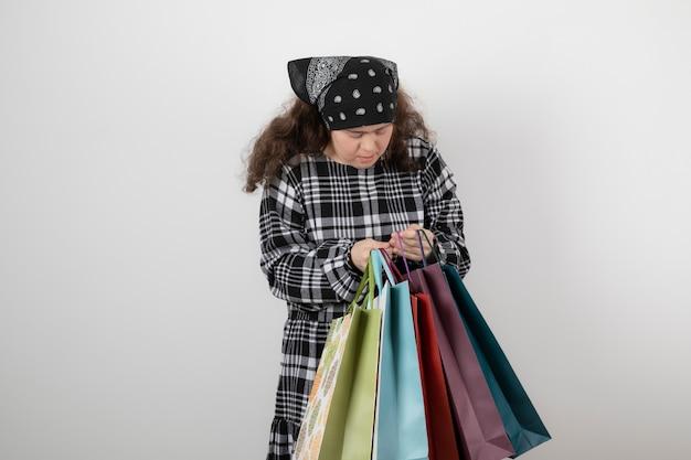 Porträt des jungen mädchens mit down-syndrom, das bündel der einkaufstasche betrachtet.