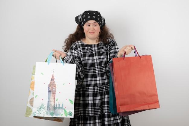Porträt des jungen mädchens mit down-syndrom, das bündel der einkaufstasche hält.