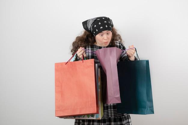 Porträt des jungen mädchens mit down-syndrom, das bündel einkaufstasche betrachtet.