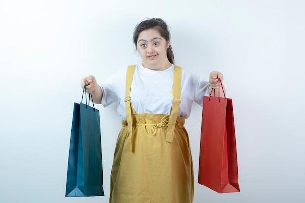 Porträt des jungen mädchens mit down-syndrom, das einkaufstaschen hält.