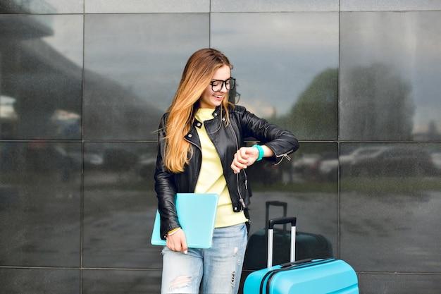 Porträt des jungen mädchens mit langen haaren in den gläsern steht draußen auf schwarzem hintergrund. sie trägt eine schwarze jacke mit jeans und hält einen laptop. sie schaut auf die uhr.