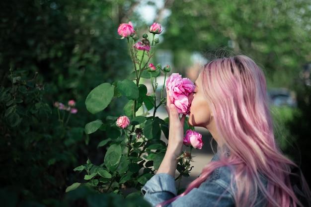 Porträt des jungen mädchens mit rosa haar, das rosenblume schnüffelt.