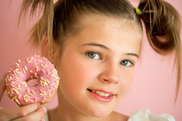 Porträt des jungen mädchens schauend durch zwei rosa schaumgummiringe