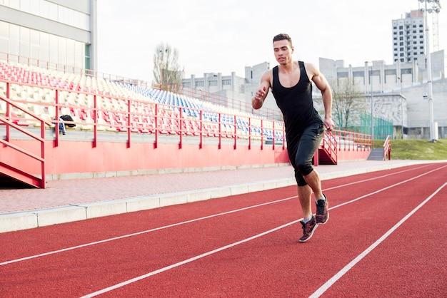 Porträt des jungen männlichen athleten der eignung, der auf rennstrecke im stadion läuft