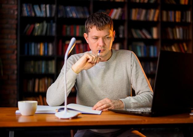Porträt des jungen männlichen denkens auf arbeitsprojekt