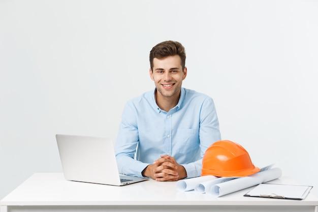 Porträt des jungen männlichen innenarchitekten oder des ingenieurs, der beim sitzen auf seinem bürotisch lächelt.