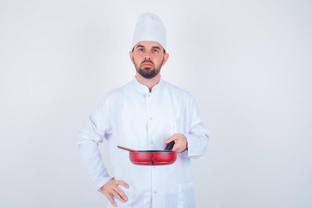 Porträt des jungen männlichen kochs, der bratpfanne mit holzlöffel in der weißen uniform hält und ernsthafte vorderansicht schaut