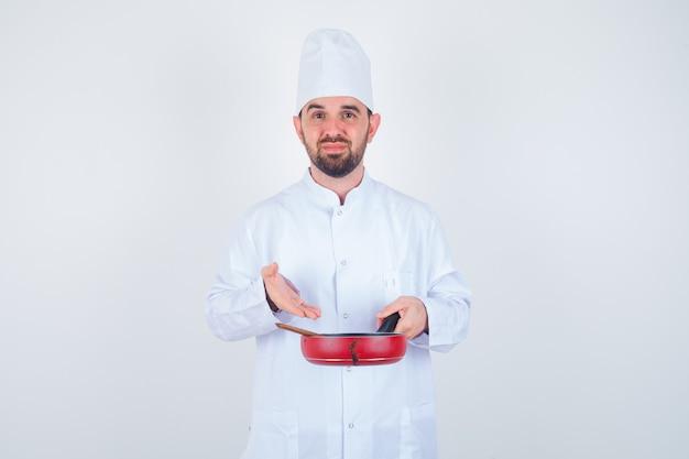 Porträt des jungen männlichen kochs, der leere bratpfanne mit holzlöffel in weißer uniform zeigt und niedergeschlagene vorderansicht schaut