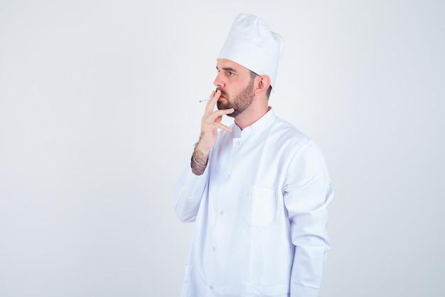 Porträt des jungen männlichen kochs, der zigarette in der weißen uniform raucht und nachdenkliche vorderansicht schaut