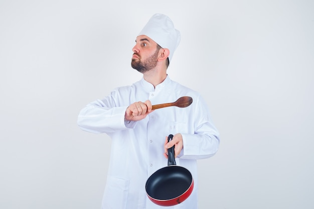 Porträt des jungen männlichen küchenchefs, der mit bratpfanne und holzlöffel in der weißen uniform droht und nervöse vorderansicht schaut