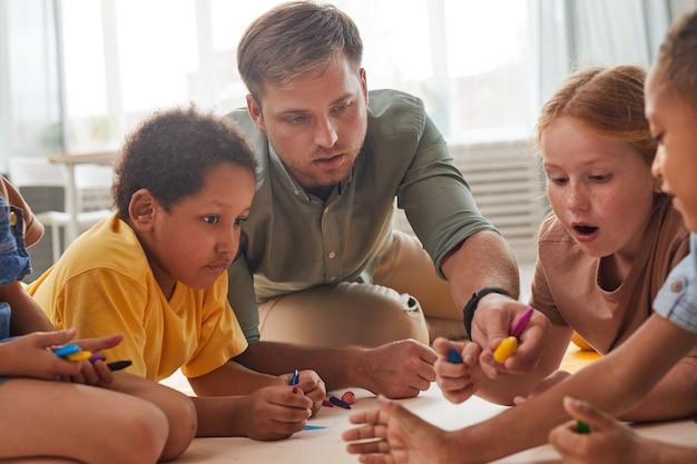 Porträt des jungen männlichen lehrers, der mit kindern arbeitet, die bilder zeichnen, während sie spaß in der vorschule oder im entwicklungszentrum haben