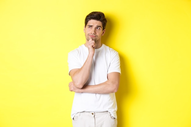 Porträt des jungen männlichen modelldenkens, das die obere linke ecke betrachtet und die wahl trifft, in der nähe des kopierraums stehend, gelber hintergrund.